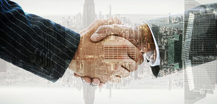 Silhouette of shaking hands over top of cityscape